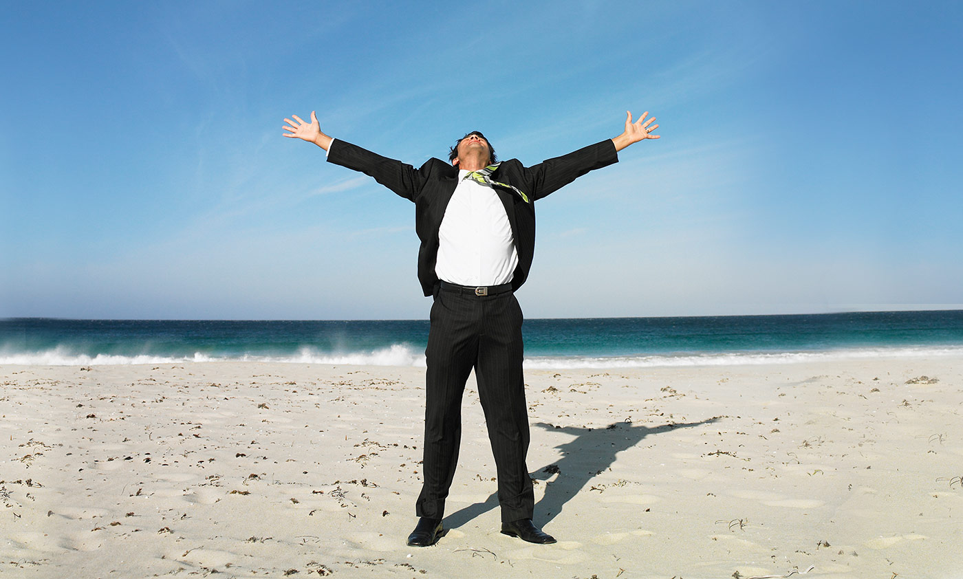 A business man stands in freedom and worship on the shores of the ocean.