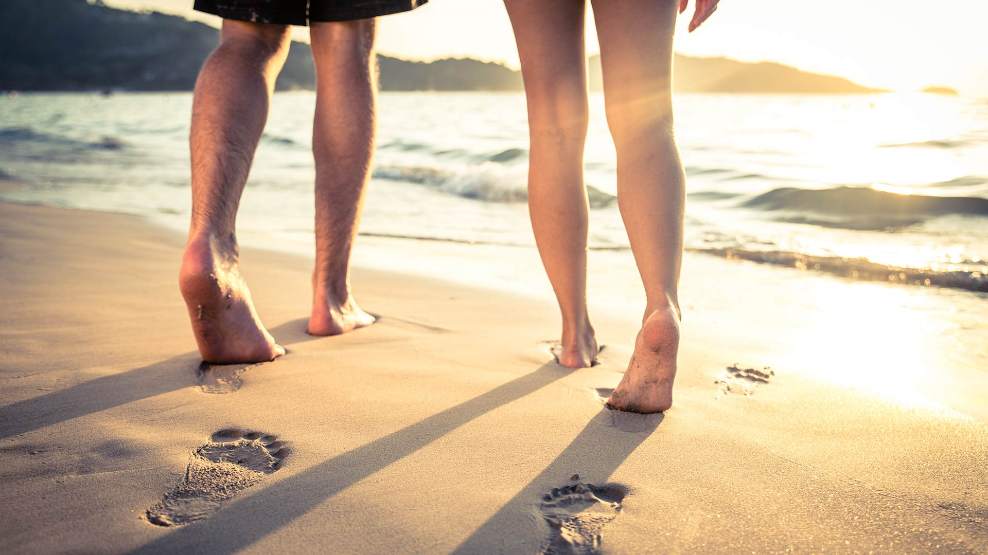 The feet of 2 people walking along the shore leave footprints in the sand.
